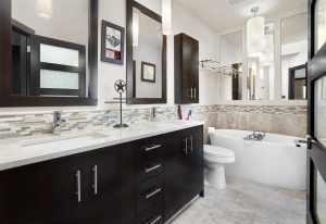 En suite bathroom, white floor, ceiling, walls and counter; black cabinets; two rectangular sinks; white tub on right