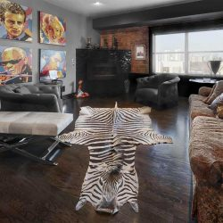 Interior condo with dark wood floor and brick around far side window; zebra rug on the floor; black fireplace in back corner and two grey chairs on either side; white bench on left, dark flower-pattern couch on right