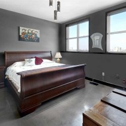 Master bedroom with grey floor and walls, white ceiling; wine-red sleigh bed with white bedding; wine-red nightstand to the left; wood crate on right; two windows on far wall