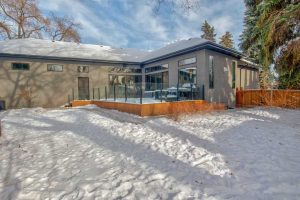 Exterior backyard in winter; wood deck with glass rails extends of grey bungalow