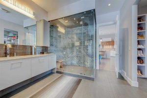 En suite bathroom with vinyl floor, white cabinets, ceiling and walls; glass shower next between open door and two sinks in front of large mirror (on left); on right, vertical shoe storage