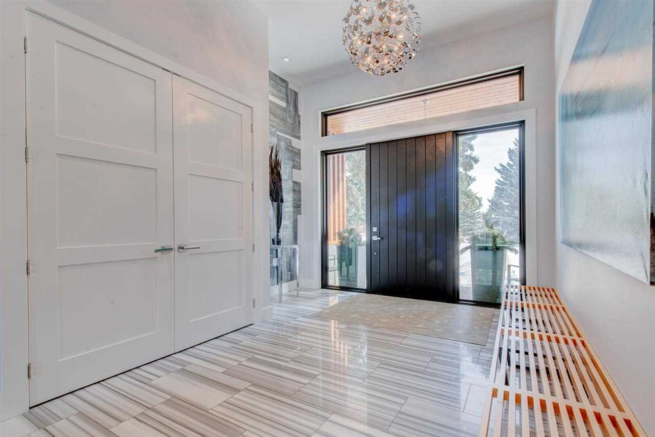 Interior entrance with white tile floor (with black lines), white closet, ceiling and walls; large black panel door with rectangular windows beside and above (and outside planters on each side); wood-slat bench inside on the right