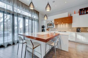 Kitchen with hardwood floor, white cabinets, ceiling and walls; rectangular wood extension off white island with sink; three stools around it, three hanging lights above