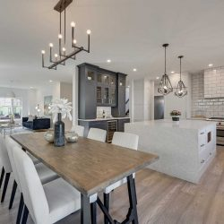 Interior main floor, light hardwood floor, white ceiling and walls; wood dining table with three chairs on either side, small chandelier above; kitchen with white waterfall island to the right