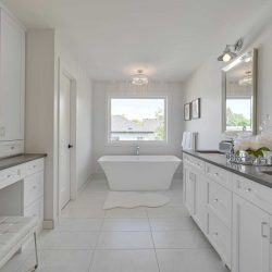 En suite bathroom, white ceiling cupboards and walls; soaker tub in front of window; makeup table and vanity mirror to left