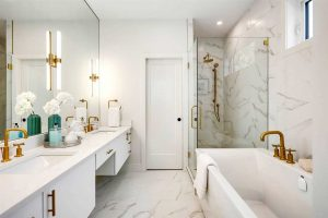 All white en suite with gold finishes and fixtures; tub on right, shower behind it; sliding door to toilet in the middle; double sinks in front of large mirror on left