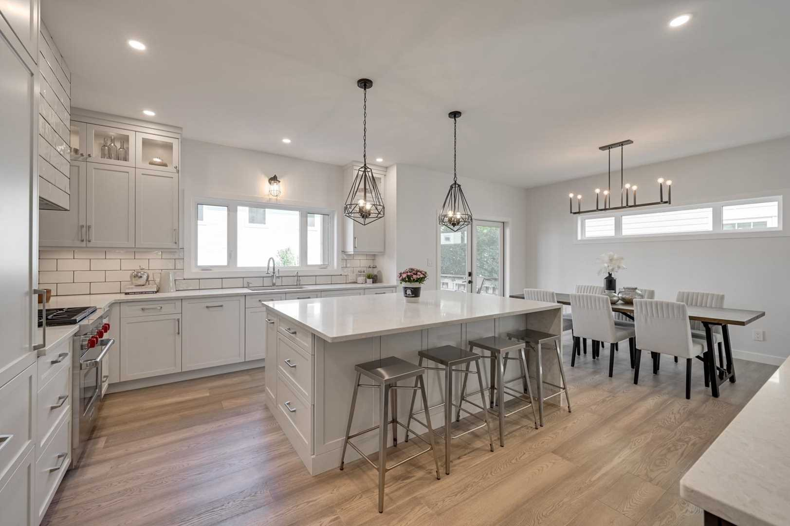 Interior kitchen, light hardwood floor, white ceiling and walls; four steel stools at white waterfall island, two light hanging overhead; white cupboards and pantry to left