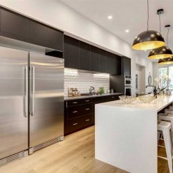 Kitchen with light hardwood floor, white ceiling; white marble waterfall island with five white stools on right, three steel dome lights above; massive fridge on left, black cabinets with white penny-tile backsplash; living room with black couch behind