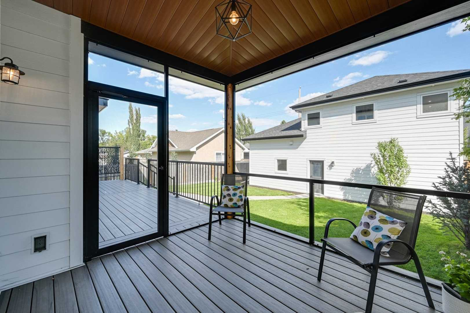 Screened-in backyard patio with door to the rest of the deck on left; two lawn chairs inside, single light above; view of one-and-a-half storey garage across green lawn
