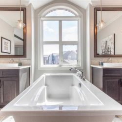 Interior en suite, white soaker tub framed centre with cove-window behind it; a sink on either side, each with a mirror and two hanging lights; dark wood cabinets