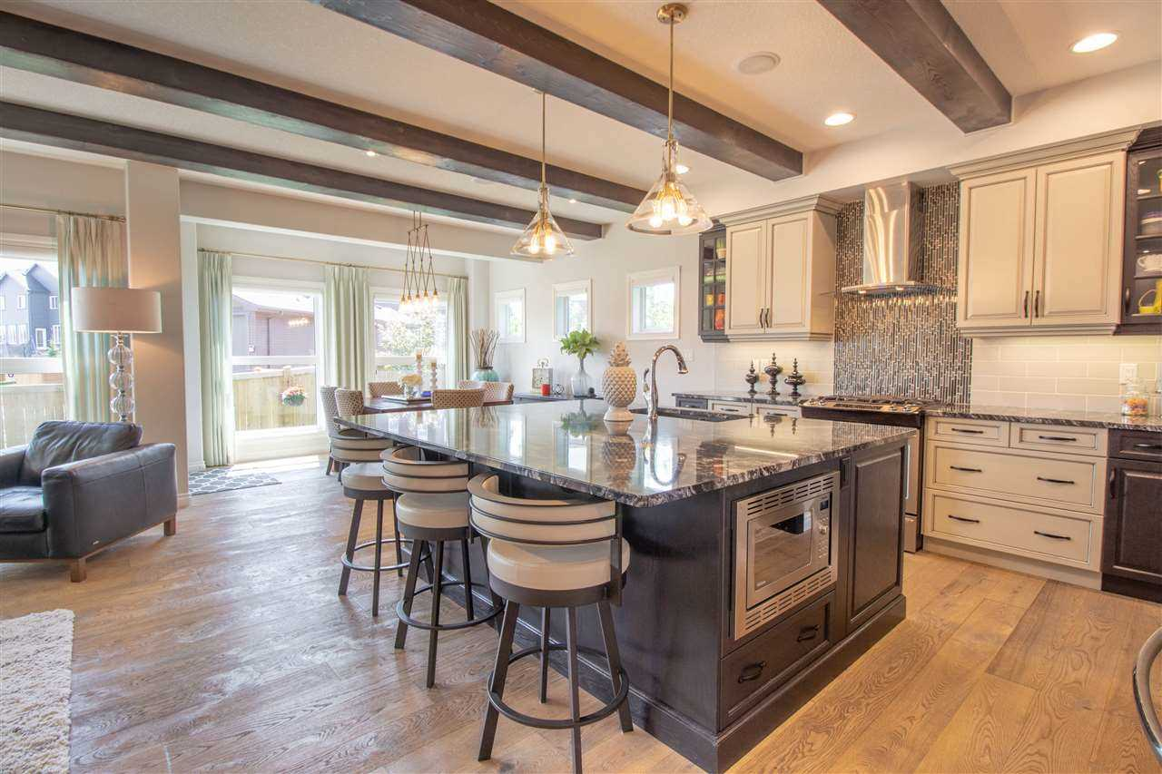 Interior kitchen with light hardwood floor, white cabinets and ceiling with cedar beams; black island with black and white countertop, microwave built into one side, three stools on the other, two hanging lights above; black and white backsplash above stove