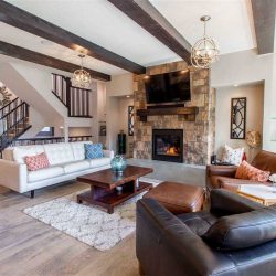 Interior living room with light hardwood floor, white walls and ceiling with decorative cedar beams and two chandeliers; dark and light leather seats on the right, white couch on left, small wood coffee table in between; stone fireplace with TV above in background