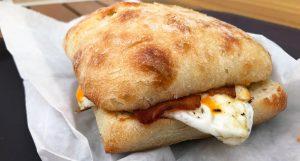 eggs and bacon breakfast sandwich on ciabatta bun