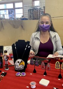A lady standing behind her table, selling indigenous art and jewelry