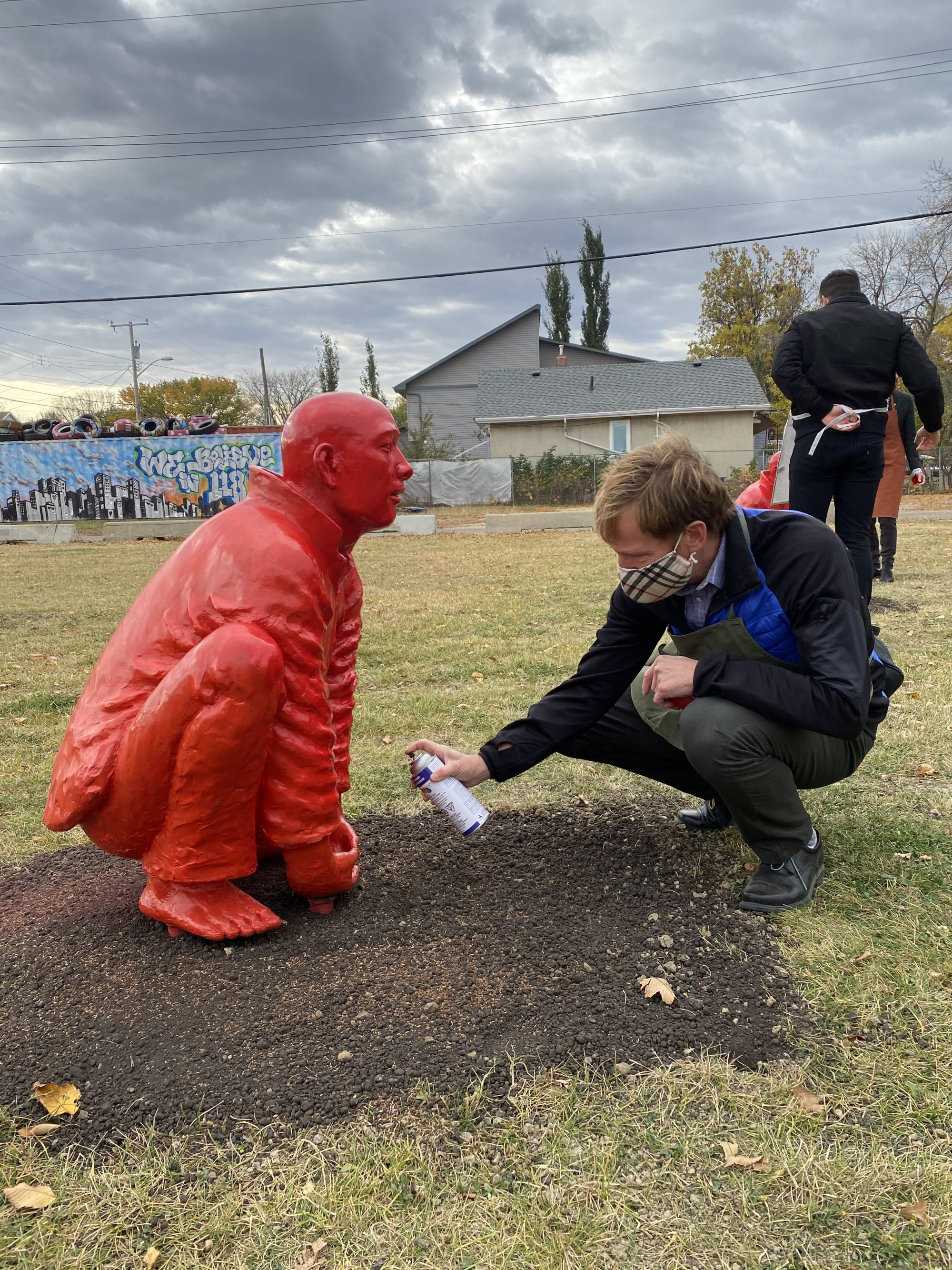 A man spray painting a statue of a man squatting down