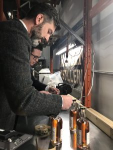 Mayor Don Iveson bottles a batch of whisky.