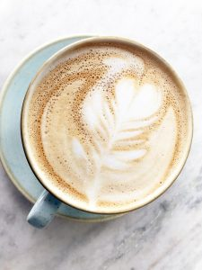 Cup of coffee with heart pattern in cream