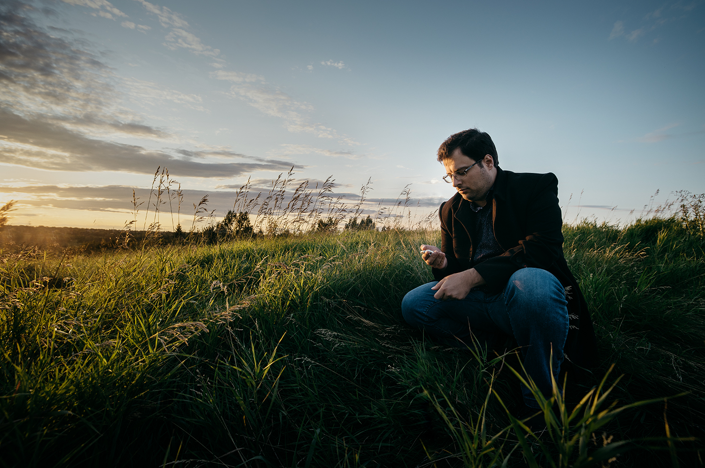 Javad Soleimani Meimandi in a green field looking at his late wife's watch.