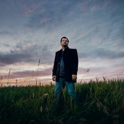 Javad Soleimani Meimandi in a green field in front of a lightly cloudy sky at sunset.