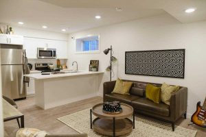 Basement suite with white walls, light grey floor and small window; white kitchen island, brown couch and circular coffee table.