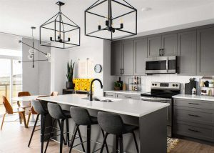 Kitchen close up; black cupboards, cabinets and island with white countertops; Edison light bulb chandeliers.