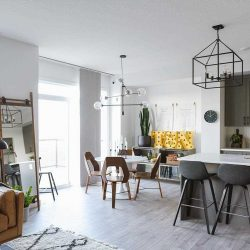 Kitchen, living and dining area; white ceiling and walls, light grey floors, wood chairs at dining table, grey and black stools at kitchen island; Edison light bulb chandeliers.