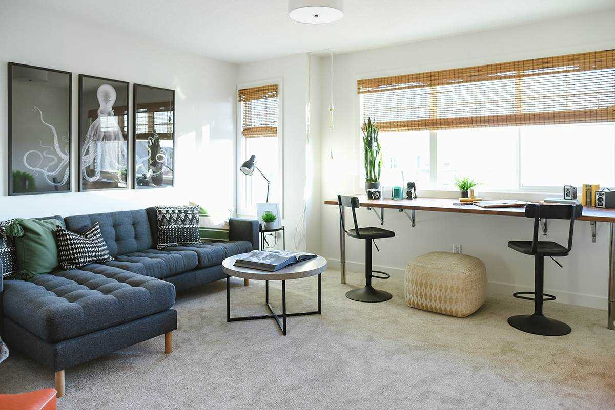 Bonus room with grey floor, white walls and a dark blue couch; bamboo blinds on large windows; black and white octopus painting on the wall.