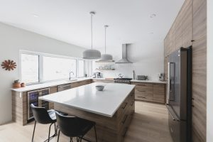 Kitchen_LargeWhiteIsland_WoodCabinetsFloor_WindowsLeft