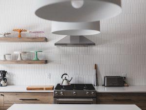 Kitchen_WhiteVerticalSubwayTile_2WhiteHangingLights_2ShelvesLeft_stainlessStove