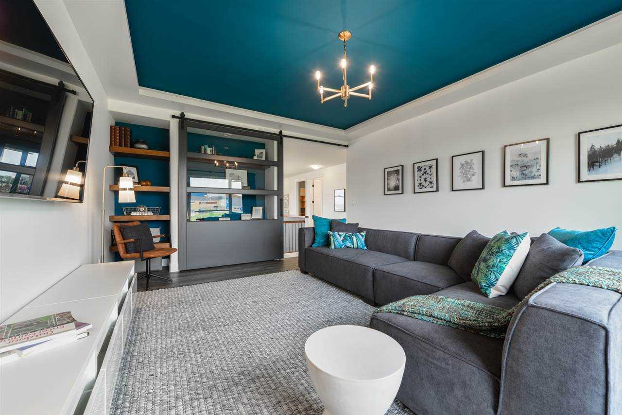 Upstairs bonus room with white walls and turquoise ceiling; chandelier and light grey carpet; bookshelf and wall-mounted TV