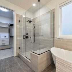 En suite bathroom with white walls, grey tile floor, opening to walk-in closet; glass wall shower with bench next to free-standing soaker tub