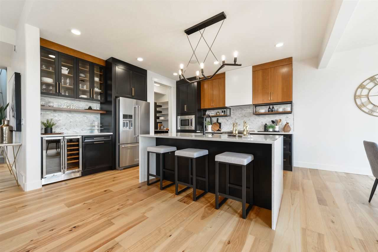 Kitchen, white walls and ceiling; black and wood cupboards, black island and stools with white counter top and seats