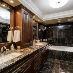 En suite with black tile floor and walls, white ceiling; double sinks in dark marble counter with dark wood cabinet on top and between; dark wood drawers below, on left; white tub in background embedded in the black tile