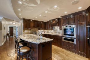 Kitchen with hickory hardwood floor, dark wood cupboards and cabinets, light ceiling with embedded lights, light marble countertops; island in foreground, rounded on seating side with four stools