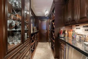 Wine cellar with light tile floor and ceiling, dark wood cabinets on right and left, dark wood door at far end; wine glasses in glass cabinet on left, marble counter with artistic jugs, wine opener and Grand Marnier on right, with mini-fridge below; wine racks beyond on each side
