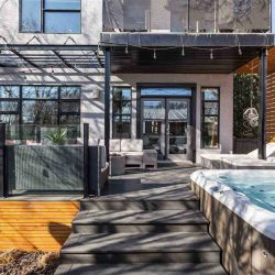 Backyard deck, light and dark grey; steps leading up to deck with second-floor patio covering half, a pergola covering the other half; string of Edison bulb lights hanging above; hot tub on the right