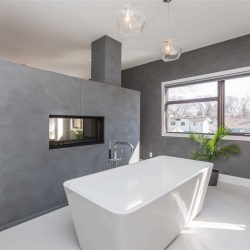 En suite bathroom with white tile floor and grey walls; grey false wall with embedded fireplace separating en suite from bedroom; white soaker tub in the middle, two hanging lights above; large window on back wall with green plant on the floor in front