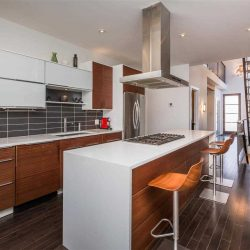 Interior kitchen with dark hardwood floor, white walls, ceiling, counters, and waterfall island with stove, hanging wood fan, and three chairs; light wood cabinets, dark grey tile backsplash