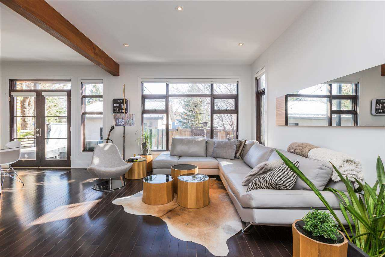 Interior living room with dark hardwood floor, white walls and ceiling with decorative wood beam; beige rug in front of light grey section couch and three drum-shaped tables on top; large windows and door on back wall, long rectangular mirror on right