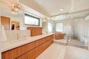 En suite bathroom, white ceiling and floor; light wood cabinets; large windows; glass-enclosed shower and tub