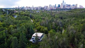 Exterior shot of three-storey home surrounded by green trees and Edmonton skyline in the background