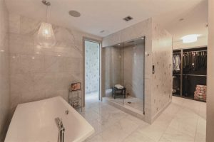 En suite with white tile floor and white marble walls, all speckled with black; freestanding soaker tub on the left, large shower with a black stool on the right; walk-through closet in background