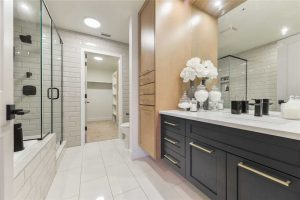 En suite bathroom with white walls and tile floor; black and beige cabinets, white countertop under large mirror; sit-down glass shower on the left