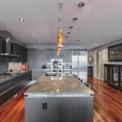 Interior kitchen with brown hardwood floor, black and grey cabinets, ceiling and walls; five yellow lights hanging over grey waterfall island; glass cabinets on the right