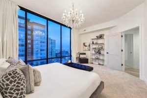 Master bedroom, white ceiling, walls, carpets and bed; hanging glass chandelier; floor-to-ceiling windows looking out to buildings on the left