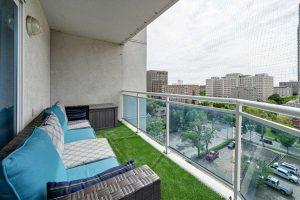 Patio on left looking out to city on right; glass railing with mesh above; fake grass on floor; plastic wicker patio couch with blue and grey cushions
