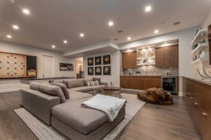 Grey couch, light brown hardwood floor, brown cabinets, embedded ceiling lights.