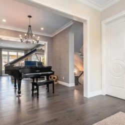 Front entrance, white walls, muted grey floors, black grand piano, chandelier.