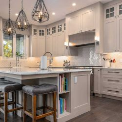 Light grey kitchen cabinets, lights hanging over quartz island, grey cushioned wood-legged stools.