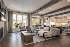 Grey floors, grey ceiling beams, light grey couches, wall-mounted TV above fireplace.